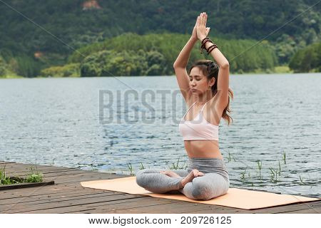 Attractive Vietnamese young woman doing exercises by the lake