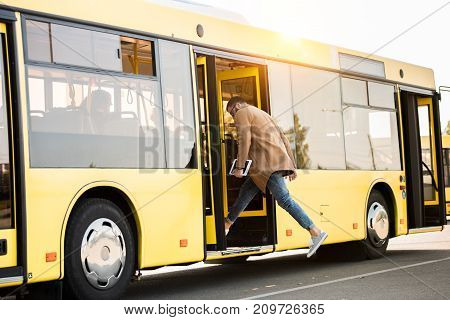 full length view of young man holding digital tablet and entering bus