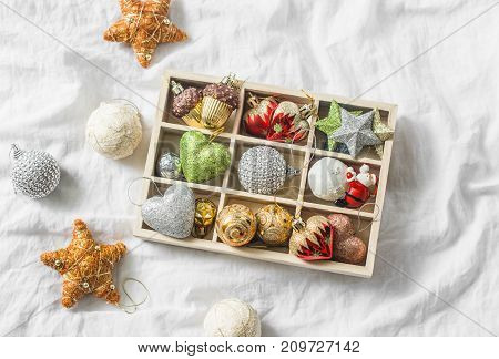 Wooden box of vintage christmas decorations on the light background top view. Christmas still life