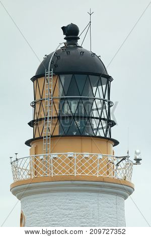The upper part of the lighthouse in cloudy sky, telephoto shot
