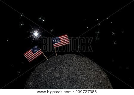 USA going back to the moon. Two American flags on the surface of a model moon in space with stars. Return to moon landing missions.