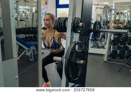 Beautiful young girl doing sit-ups with a barbell in the gym