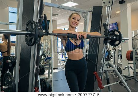 Charming young girl posing with a barbell in the gym. Fitness
