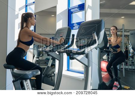 Sexy young girl is engaged on a bicycle simulator in the gym