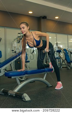 Sporty girl doing exercises with dumbbells in the gym. Fitness. Sport. Health