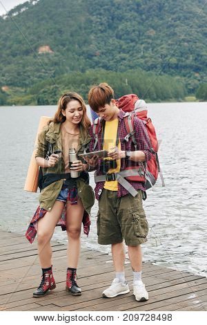 Two backpackers using application on tablet computer when traveling