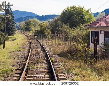 The railroad passing through a wooded area and leaving far away from the village of Prahova in Romania