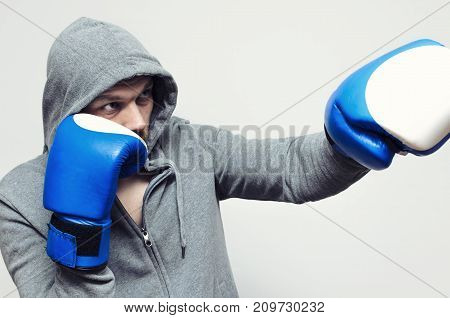 Boxer in large combat gloves and a sports jacket with a hood