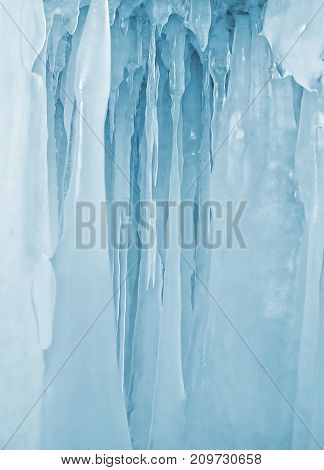 Blue icicles background on the ice wall on Baikal lake at winter
