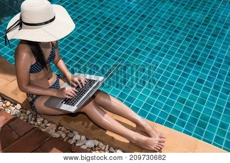 Asian Young Woman In Big Hat Relaxing On Poolside With Laptop Computer