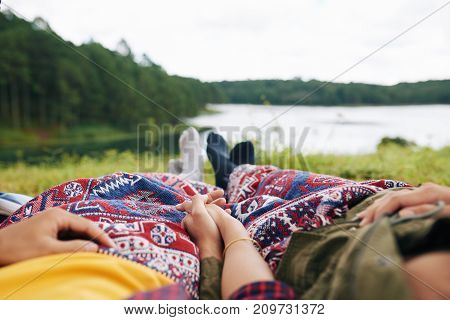 Couple relaxing on ground by river, focus on hands