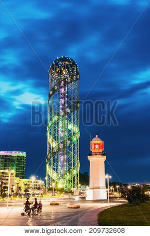 Batumi, Adjara, Georgia - May 26, 2016: Illuminated Alphabet Tower And Pitsunda Lighthouse At Promenade Near Miracle Park, Amusement City Park On Evening Or Night Sky Background. Blue Hour. Modern Urban Architecture