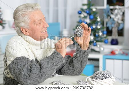 Portrait of senior man in Santa hat preparing for Christmas sitting at the table at home