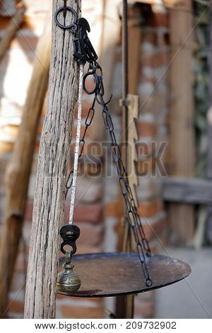 old weight scale hanging on a pole