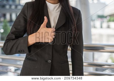 close up hand of business woman showing thumb up in the city business success concept