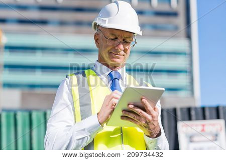 Senior engineer man in suit and helmet working on tablet pc