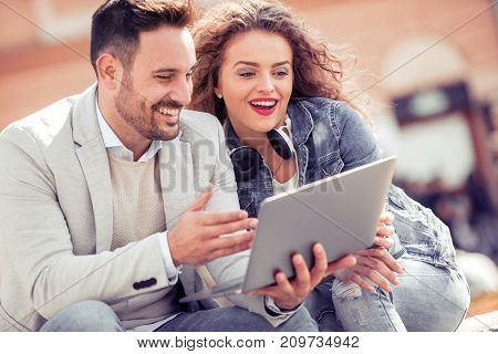 Portrait of attractive couple with tablet computer in urban background.