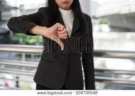 close up hand of business woman showing thumbs down in the city