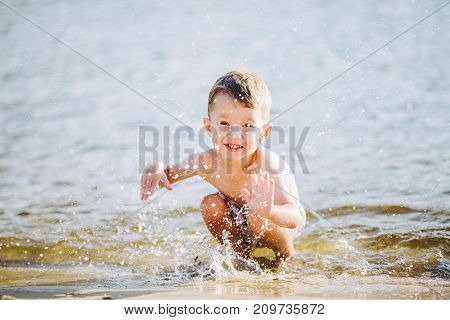 Boy Child Playing Makes Splashes, Beats Hands On The Water In The River At Sunset