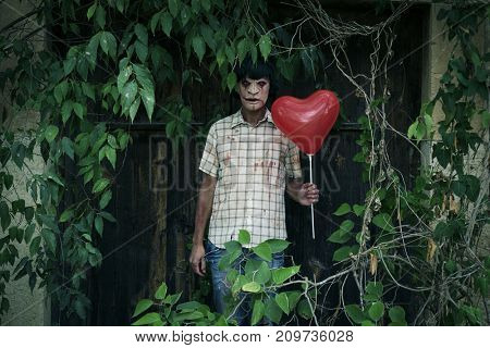 a scary disfigured man with a red heart-shaped balloon in front of the door of an abandoned house covered by weeds
