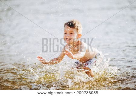 boy child playing makes splashes beats hands on the water in the river at sunset of the day