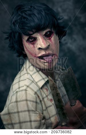 closeup of a scary disfigured man holding some rusty and bloody cleaver and knife in his hands