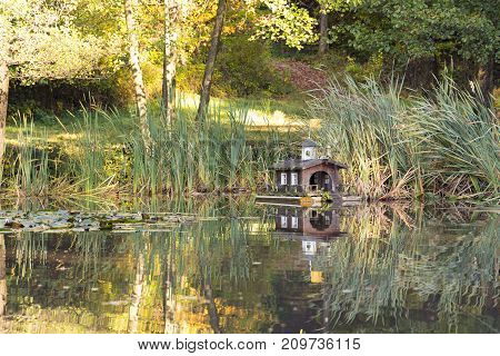 cute miniature handcrafted wooden house on lake pond with reflection hiking trip environment housing for animals birds ducks