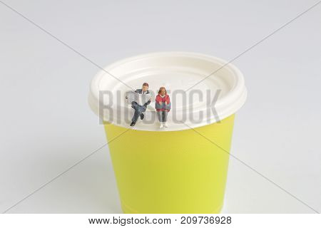 Mini Figure Sitting And Read On Paper Cup