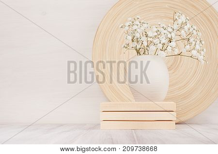 Soft home decor of beige bamboo dish and white small flowers in ceramic vase on white wood background. Interior.