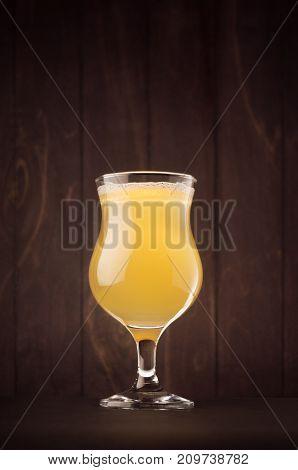 Tulip beer glass with muddy weizen on dark wood board vertical. Template for advertising design branding identity restaurant menu cover.