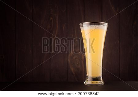 Pilsner beer glass with muddy weizen on dark wood board copy space. Template for advertising design branding identity restaurant menu cover.