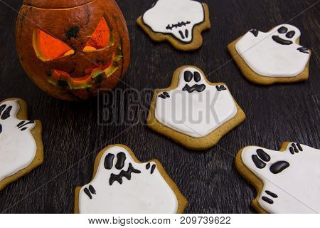 Halloween holiday cookies in the shape of ghosts. Halloween biscuit with moster pumpkin.