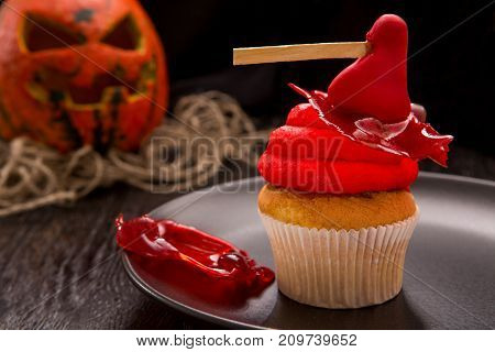 Halloween red one cupcake with ax on black plate. Cupcake with blood and pumpkin. Halloween decorated cookie on dark wooden table. Close up