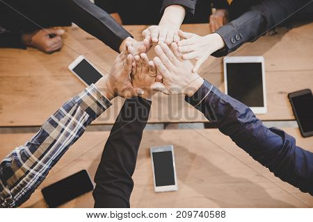 Top view executive business people group team happy showing teamwork and joining hands or giving five after meeting partner business in office. Business and Teamwork Concept.