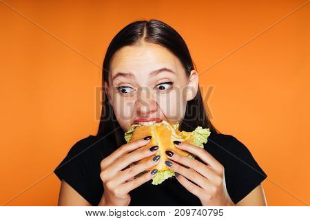 young beautiful girl wants to lose weight, but eagerly eats a harmful high-calorie hamburger
