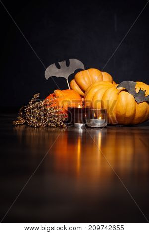 a composition for decorating a house for halloween, lie yellow and orange pumpkins, candles burn, drawings of black bats
