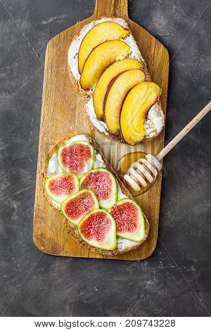 Wholemeal Toasts with Cream Cheese Fresh Ripe Figs and Peaches on Wood Cutting Board. Drizzled with Honey. Dark Stone Background. Flat Lay