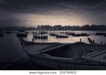 Fishing boat on the beach at sunrise with Alexandria skyline in far distance and cloudy sky