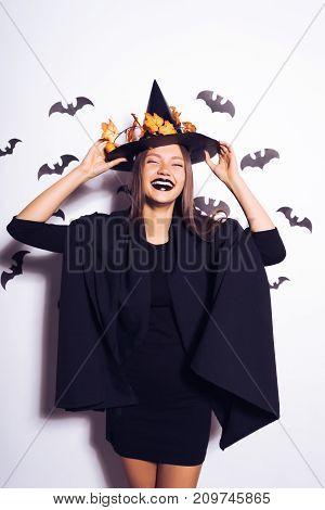 young sexy gothic woman in the image of a witch in halloween, in a big black hat, adorned with yellow leaves, laughs