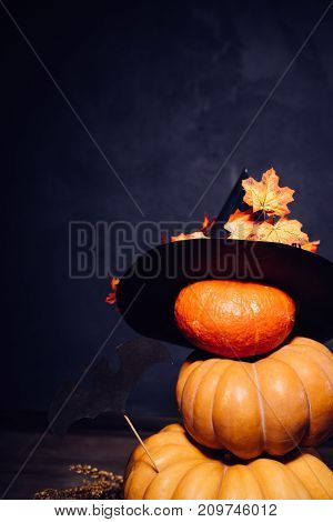 a composition for decorating a house for halloween, lie yellow and orange pumpkins, a black witch hat, drawings of black bats