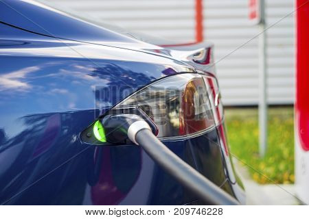 Modern Electric Car Plugged To Charging Station In A Parking Lot.