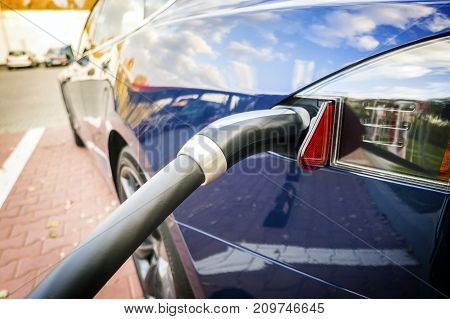 Modern Electric Car Plugged To Charging Station.