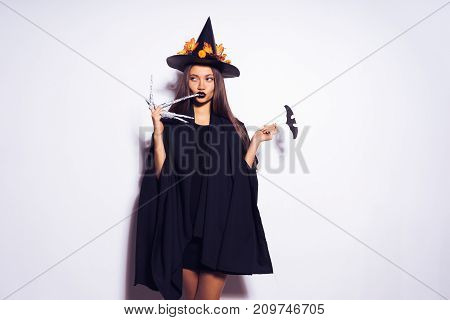 A young sexy gothic woman in the shape of a witch in halloween, in a big black hat, adorned with yellow leaves, looks cool