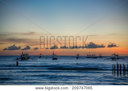 Evening sunset of a calm sea with silhouettes of boats in the distance. Malay, Philippines