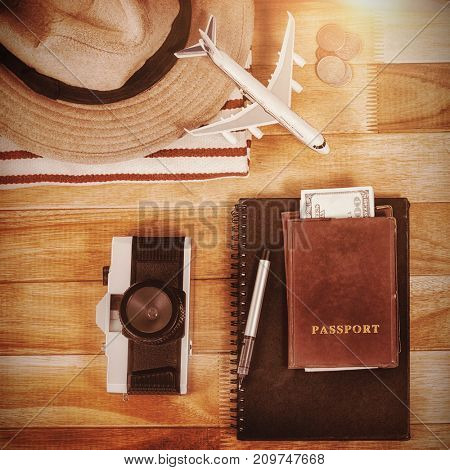 Overhead view of diary with currency by digital tablet and luggage