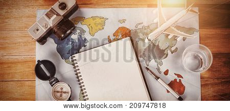 Overhead view of diary by toy airplane and camera on map at table