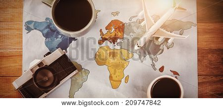 Overhead view of coffee cups with toy airplane and camera on map at table