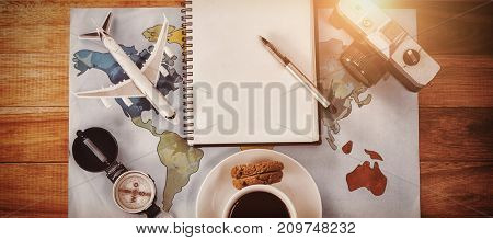 Overhead view of coffee cup with camera and diary map at table