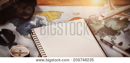 High angle viewof Diary by camera and toy airplane on map at table