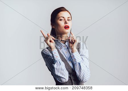 a girl with red lips takes off her glasses and points her finger to the side and looks  into the camera